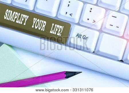 Text sign showing Simplify Your Life. Conceptual photo focused on important and let someone else worry about less ones White pc keyboard with empty note paper above white background key copy space. poster