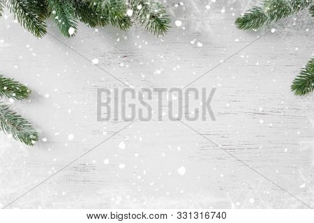 Pine Leaves Decorated As A Frame On A White Wooden Background  With Snowflakes. Merry Christmas And
