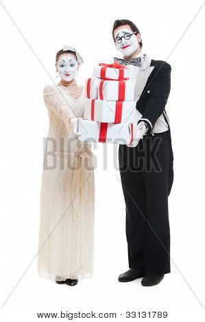 funny mimes with gift boxes over white background in studio