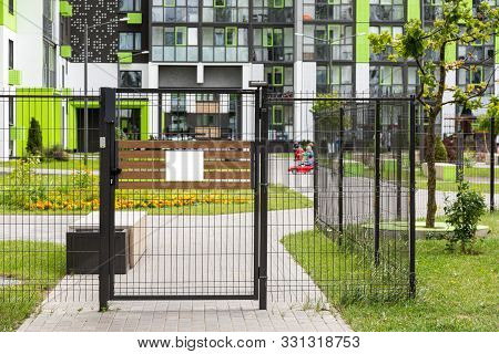 Gate With Blank Tablet Of Entrance In Yard Of Apartment Building