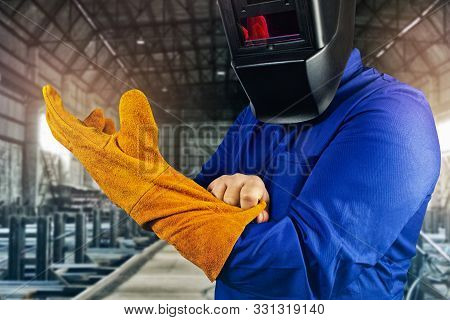 Photo Of A Fully Equipped Welder In Robe, Mask Pulling On Orange Protective Glove Standing On Steel