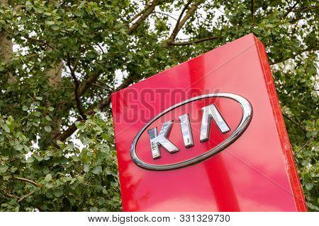 Minsk, Belarus - July 15, 2019: Kia Logo Kia Dealership Sign Against Green Leaves On Trees. Kia Is S