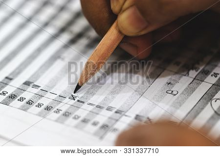 Concept Of Measurement And Evaluation. Hand Of Teacher Using Pencil Written Text On Paper Of Final G