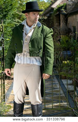 Portrait Of Handsome Gentleman Dressed In Vintage Costume And Top Hat Standing In Stately Home Court