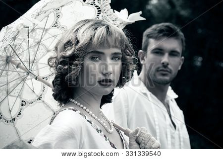 Handsome Young Couple In Vintage Clothing With Beautiful Woman Looking At Camera As Handsome Man Wat