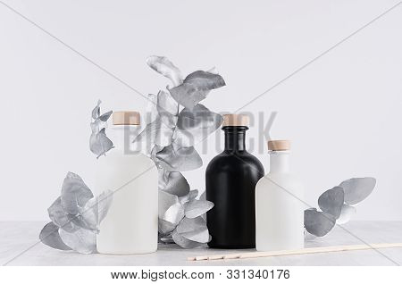 Blank Cosmetic Glass White, Black Bottles With Beige Bungs Decorated Silver Twig, Leaves As Mock Up