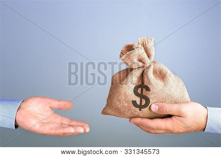 Man Holds, Gives A Bag Of Money In Hand Like A Bonus. Businessman Holding Bag Of Money In Hand Offer