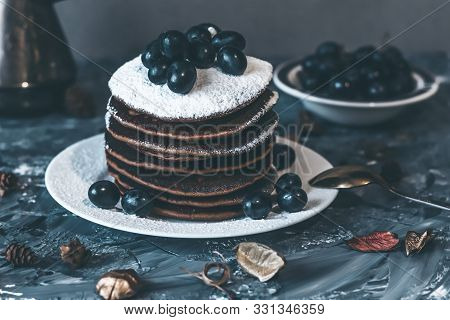 Pancakes On A White Plate In Powdered Sugar With Grapes On A Gray Background.