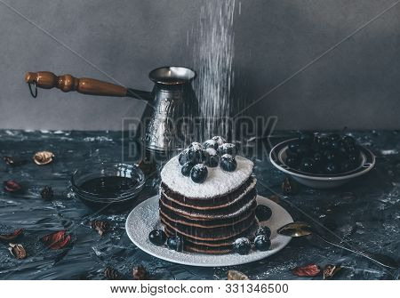 Pancakes On A White Plate In Powdered Sugar With Grapes On A Gray Background