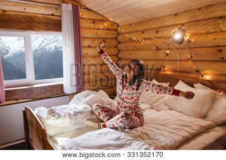 Dreamy Christmas vacation in log house with winter mountains landscape in window. Young girl wearing traditional pajamas relaxing in bed inside cozy cabin.