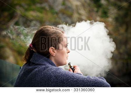 Young Brunette Caucasian Woman Smoking A Vape Ecigarette While Standing On A Balcony Overlooking The