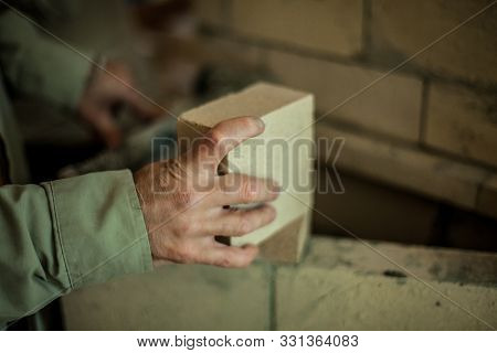 Brickmasons Hand Holding A Brick In Front Of A Brick Wall