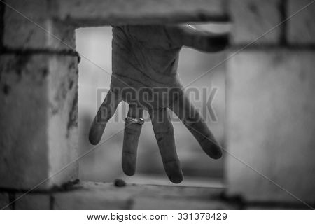 Hand With Wedding Ring Being Seen From A Whole In A Brick Wall, In Black And White