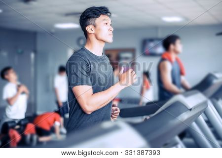 Asian Young Atheletic Boy In Sportswear Running On Treadmill At Gym With Friends