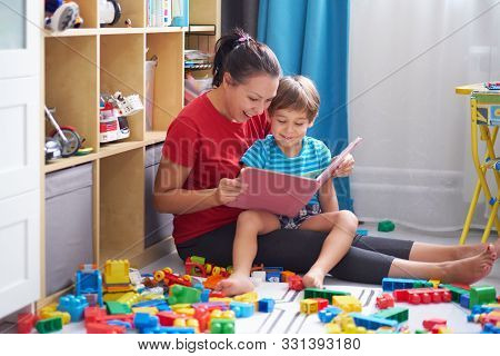 Kid Boy And His Mother Read A Book On Floor At Home