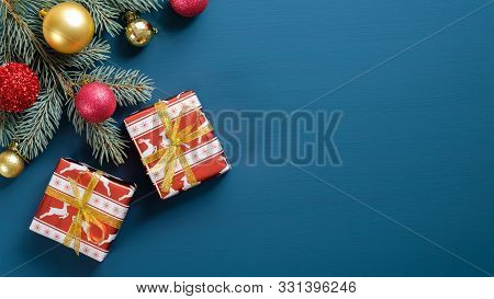 Christmas Greeting Card Mockup With Flat Lay Gift Boxes, Fir Tree Branches, Baubles On Blue Backgrou