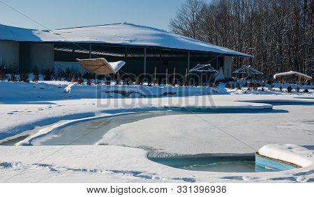 View Of Backyard Of Private House Or Sanatorium With Swimming Pool Or Hot Spring Covered With Snowdr