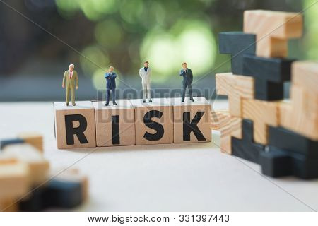Miniature People Group Of Businessmen Stand On Cube Word With Risk. Risk Analysis For Investment. Th