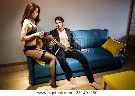 Young Sexy Couple In Living Room. Picture Of Woman Sitting On Edge Of Sofa And Pour Wiskie Into Glas