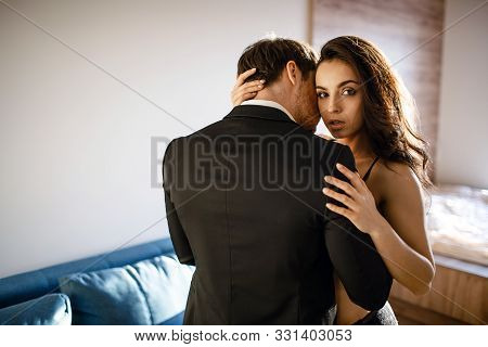 Young Sexy Couple In Living Room. Beautiful Attractive Young Woman In Black Lingerie Embrace Man And