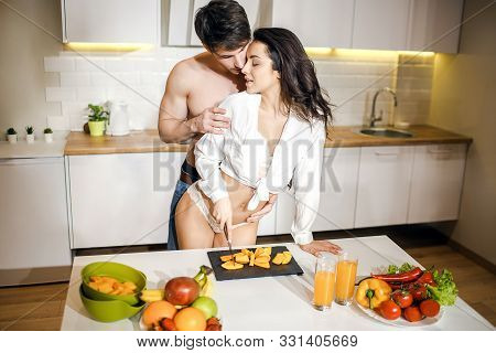 Young Sexy Couple After Intimacy In Kitchen In Night. Hot Seductive Woman Stand At Table And Cut Fru