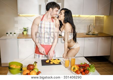 Young Sexy Couple After Intimacy In Kitchen In Night. Cheerful People Stand Close And Smile. Guy In