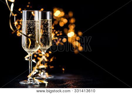 Champagne Glasses With Golden Ribbon And  Sparkles On Black Background - New Year Celebration