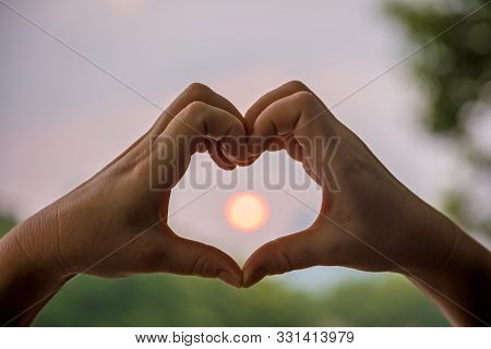 Woman`s Hands Catching Sun While Making Heart Shape At Dusk