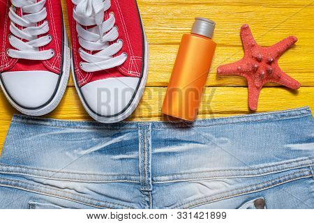 Summer Vacation Flat Lay Background. Red Gum Shoes, Jeans Short, Suntan Cream And Star Fish On Yello