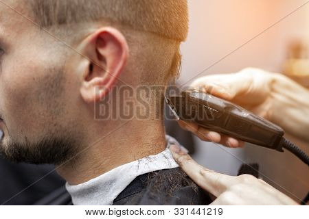 Young Guy Makes A Short Haircut In A Barbershop With A Trimmer, Close-up