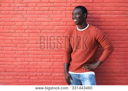 African Young Man Smiling And Leaning On Red Wall