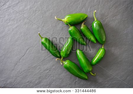 Ingredients For Salsa- Jalapenos, A Tomato And An Onion- Rest On A Gray Slate Cutting Board- Food Pr