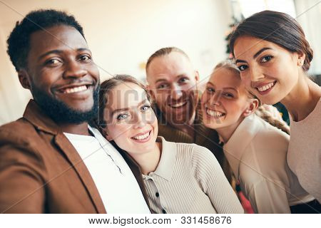 Multi-ethnic Group Of Elegant Adult People Smiling At Camera While Taking Selfie Photo During Christ