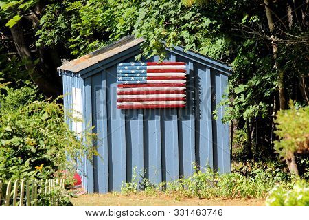 Small Garden Shed With Piece Of Stockade Fencing Painted Like A Flag On The Side.