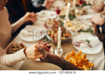 Closeup Of People Sitting At Dining Table On Christmas And Joining Hands In Prayer, Copy Space