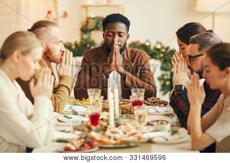 Portrait Of African-american Man Saying Grace Sitting At Dinner Table During Christmas Banquet With