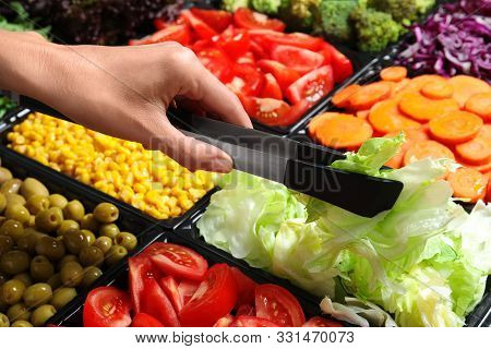 Young Woman Taking Iceberg Lettuce From Salad Bar, Closeup