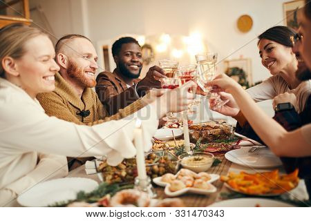 Multi-ethnic Group Of People Raising Glasses Sitting At Beautiful Dinner Table Celebrating Christmas