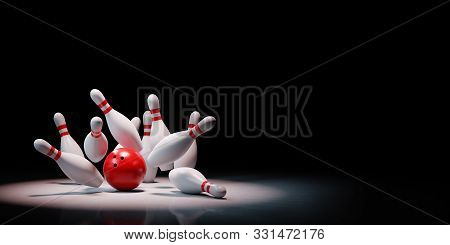 Strike Of Red And White Bowling Skittles With Red Ball Spotlighted On Black Background With Copy Spa