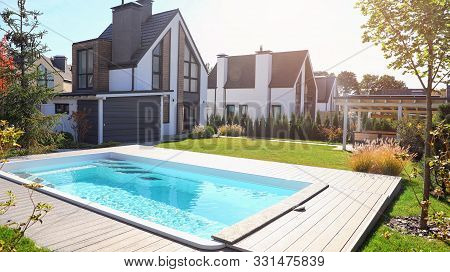 New Modern House With Backyard Swimming Pool On Sunny Day