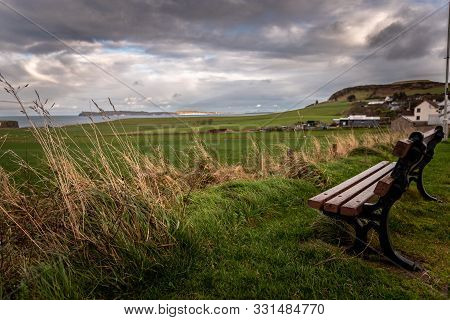 Lonely Bench In A Cold And Windy Coastal City, Pointing To The Sea With Dramatic Cloudy Sky While Gr