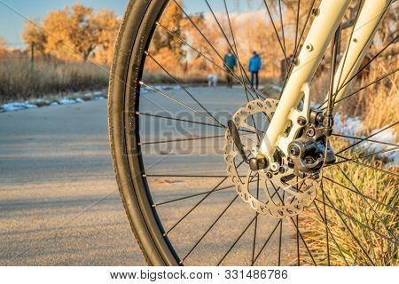 Bike trail with a walking couple in late fall scenery as seen through a bike front wheel - Poudre RIver Trail in northern Colorado