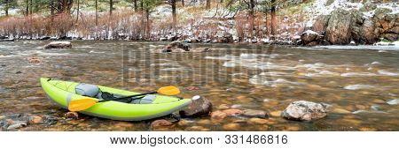 inflatable whitewater kayak with a paddle on shore of mountain river after springtime snowstorm - panorama of Poudre River in northern Colorado