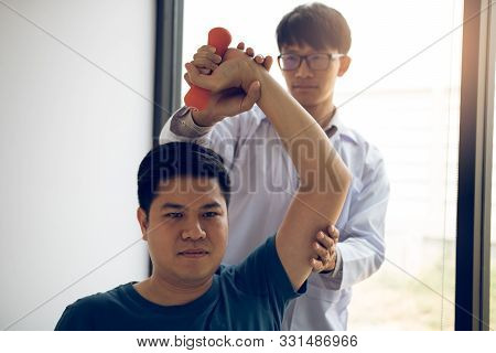 Asian Physiotherapists Help Raise Arms For Patients To Raise Dumbbells Through His Rehabilitation In