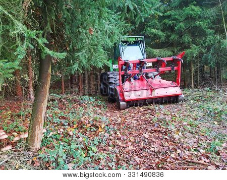 Pilsen / Czech Republic - October 31, 2019: Forestry tractor Merlo Tre Emme MM 350 X tool carrier with mulcher and stump cutter head working in forest. Lumber industry in European Union.