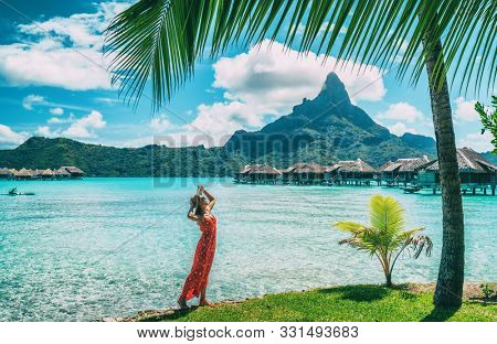 Bora Bora Tahiti vacation woman at luxury hotel in French Polynesia, tourist enjoying tropical summer resort lifestyle.