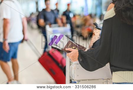 Closeup Of Girl Holding Passport And Boarding Pass At Airport