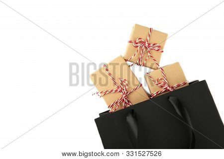 Black Shopping Bag With Gifts Isolated On White Background With Copy Space.