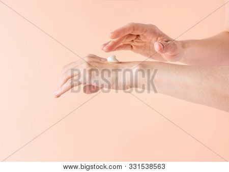 Young Caucasian Woman Rubbing In Hands Pure Organic Coconut Oil On Pink Background. Body Skin Care N