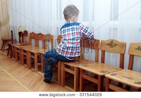 Cute Alone Caucasian Baby Boy With Fair Hair Sits On The Chair, Back To The Viewer, Face To The Wind